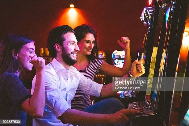 friends playing the slots - casino stock pictures, royalty-free photos & images