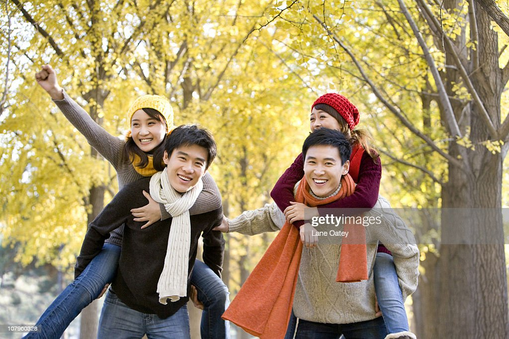 Friends Playing Together in a Park in Autumn : Stock Photo