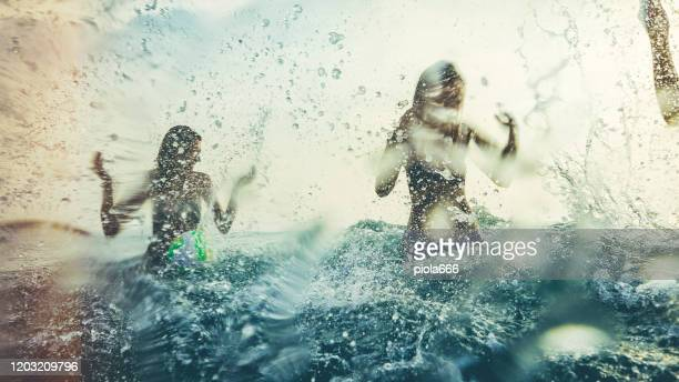 friends playing together in the sea, splashing and diving during a summer sunset - splashing stock pictures, royalty-free photos & images