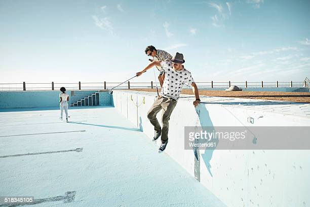 friends playing urban golf in empty swimming pool - hommes nus photos et images de collection