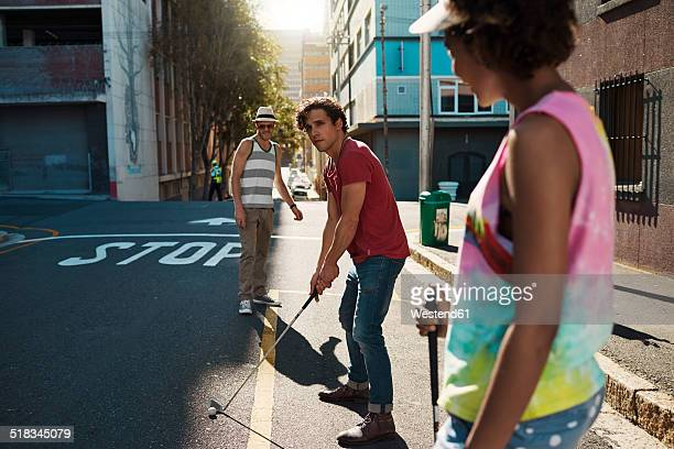 Friends playing urban golf in the city