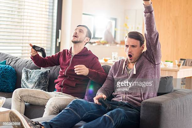 friends playing video game - defeat stock photos and pictures