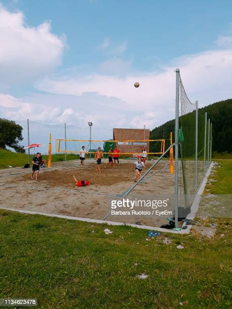 friends playing volleyball against sky - beach volley foto e immagini stock