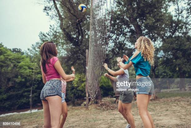 Friends playing volleyball at public park