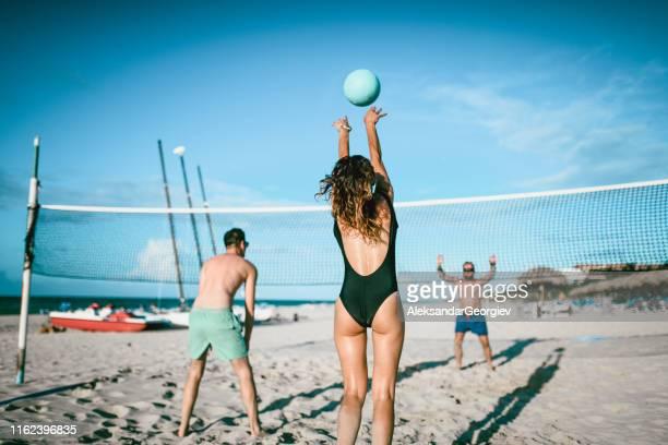 freunde spielen volleyball am strand - strand volleyball der männer stock-fotos und bilder