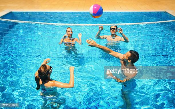 Friends playing volleyball in a pool.