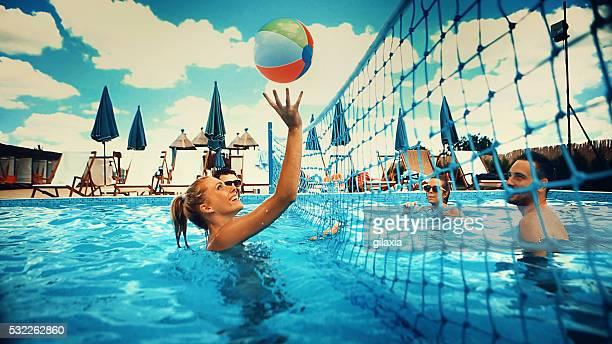Freunde spielen Sie eine Runde volleyball im pool.