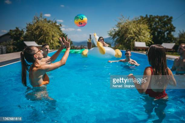 friends playing volleyball in the swimming pool - kids pool games stock pictures, royalty-free photos & images