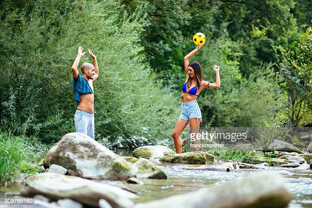 friends playing volleyball on the river