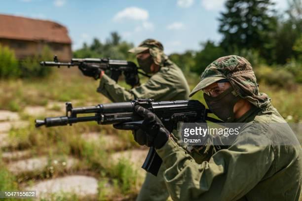 friends playing warfare game with airsoft guns - air soft gun foto e immagini stock