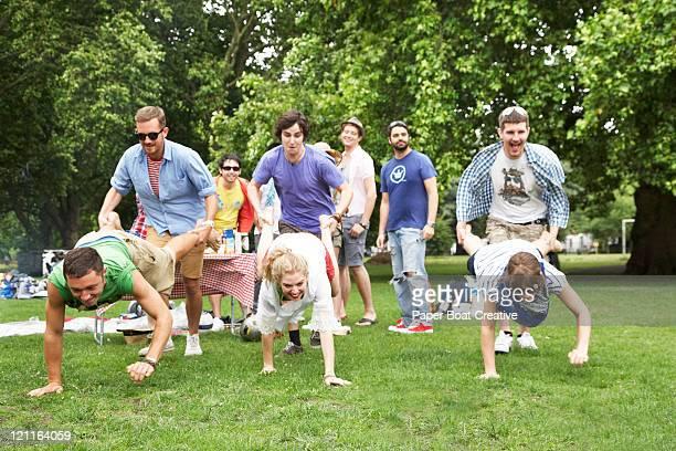 Friends playing wheel barrow race in park