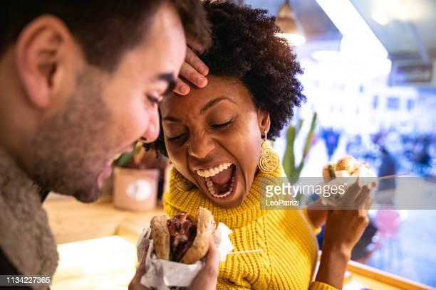 vrienden spelen tijdens het eten van een hamburger - burger menselijke rol stockfoto's en -beelden