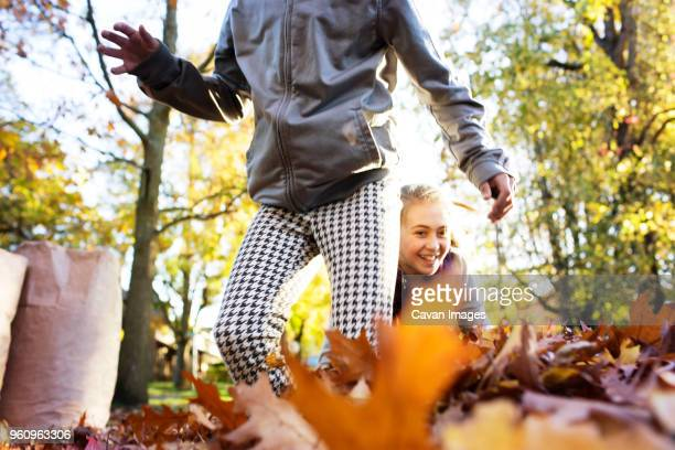 Friends playing with autumn leaves on street