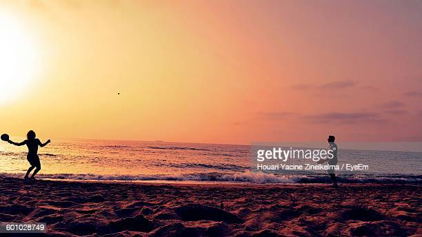friends playing with ball on beach against sky during sunset - oran algeria photos et images de collection