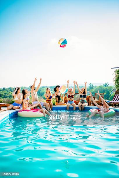 friends playing with beach ball in swimming pool - pool party stock pictures, royalty-free photos & images