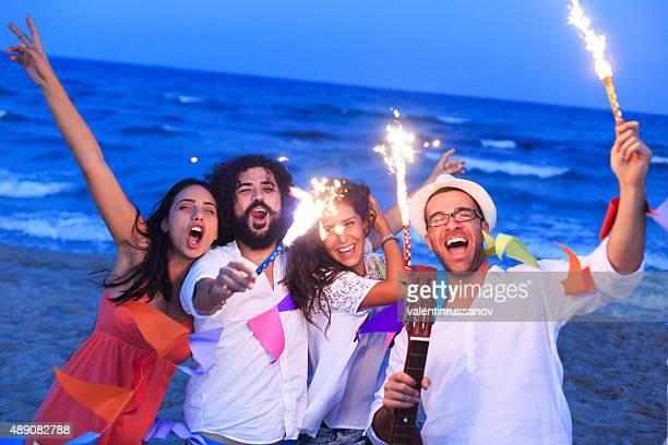 Amigos jugando en la playa y fuegos artificiales