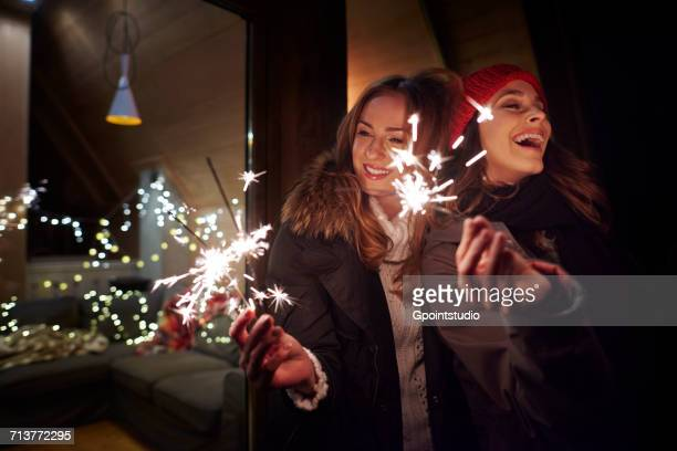 Friends playing with sparklers by chalet
