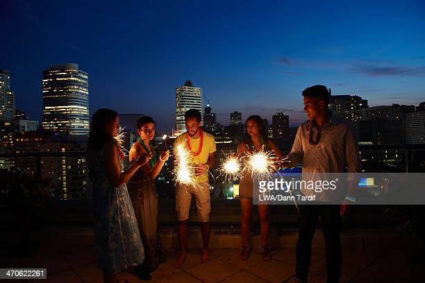 Friends playing with sparklers on urban rooftop