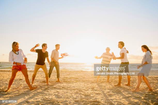 Friends playing with water gun and water balloons on beach