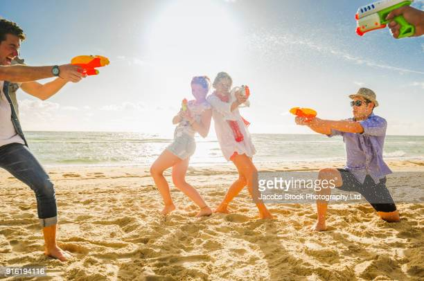 Friends playing with water guns on beach