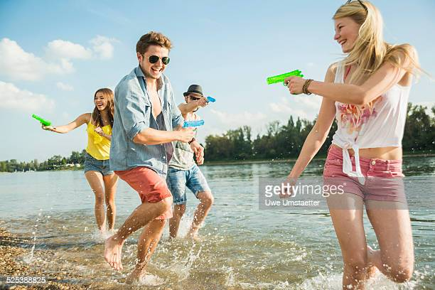 Friends playing with water pistols in lake