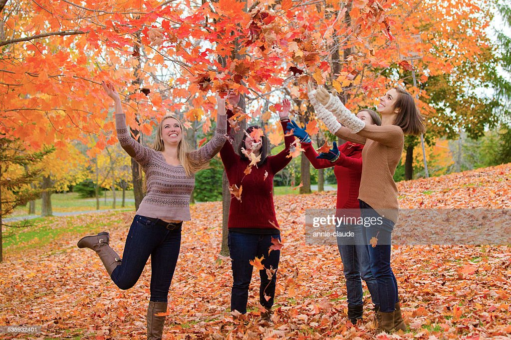 Friends plying in automn leaves : Stock Photo