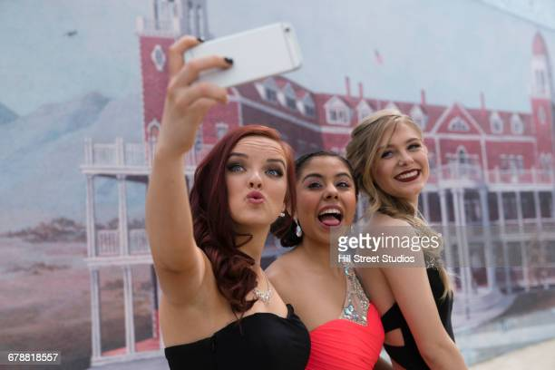 Friends posing for cell phone selfie at prom