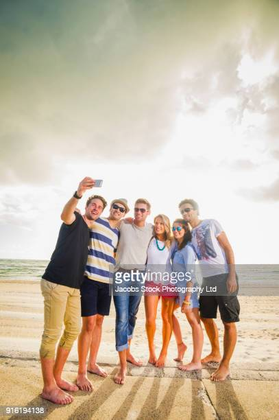 Friends posing for cell phone selfie on beach