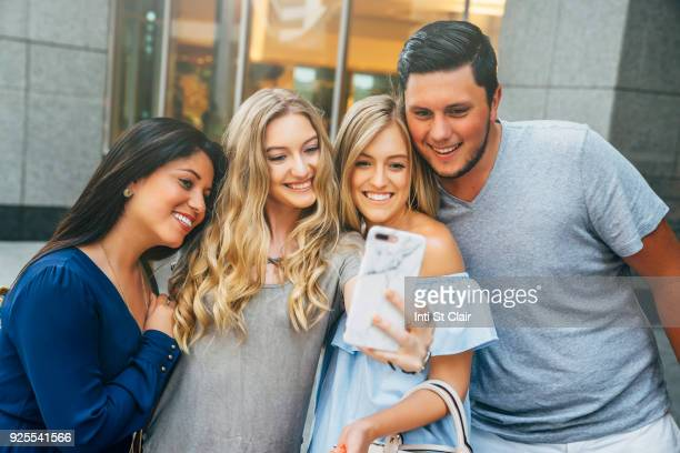 Friends posing for cell phone selfie