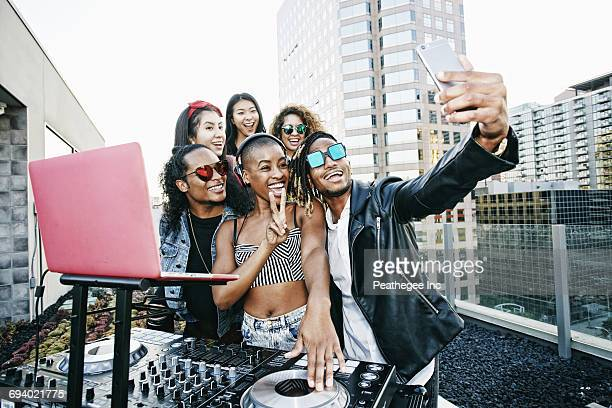 Friends posing for cell phone selfie with DJ on urban rooftop