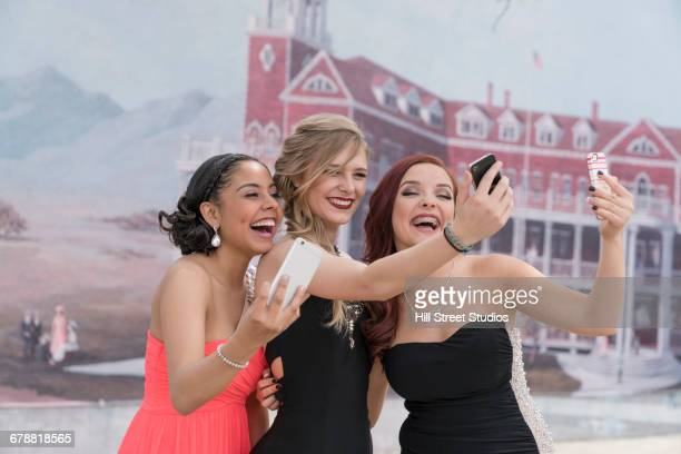 Friends posing for cell phone selfies at prom