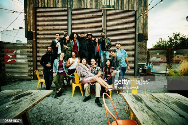 friends posing for group photo during party at outdoor restaurant - ethnicity stock pictures, royalty-free photos & images