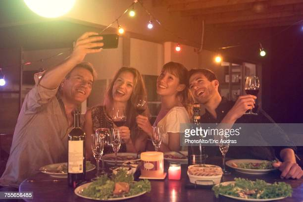 Friends posing for group selfie at dinner party