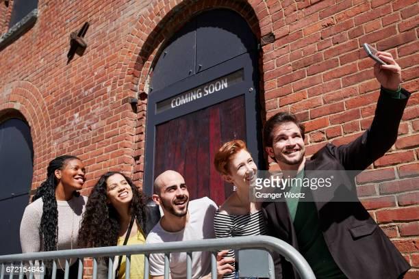 Friends posing for selfie behind railing