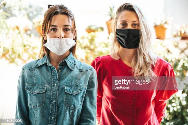 friends posing looking at camera with protective face mask - mistake stock pictures, royalty-free photos & images