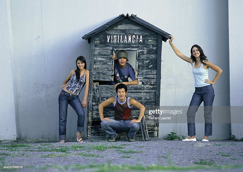 Friends posing next to wooden house. : Stockfoto
