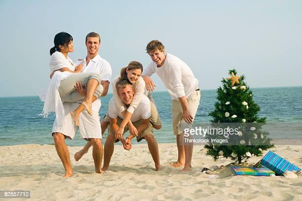 Friends posing with Christmas tree on beach