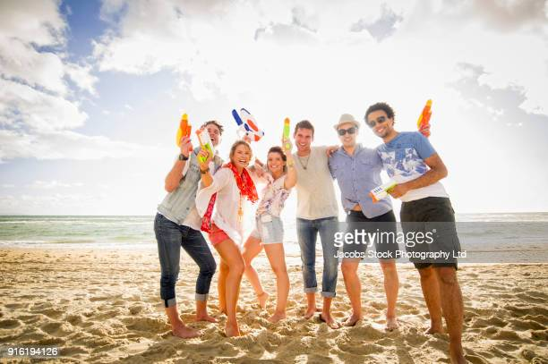 Friends posing with water guns on beach