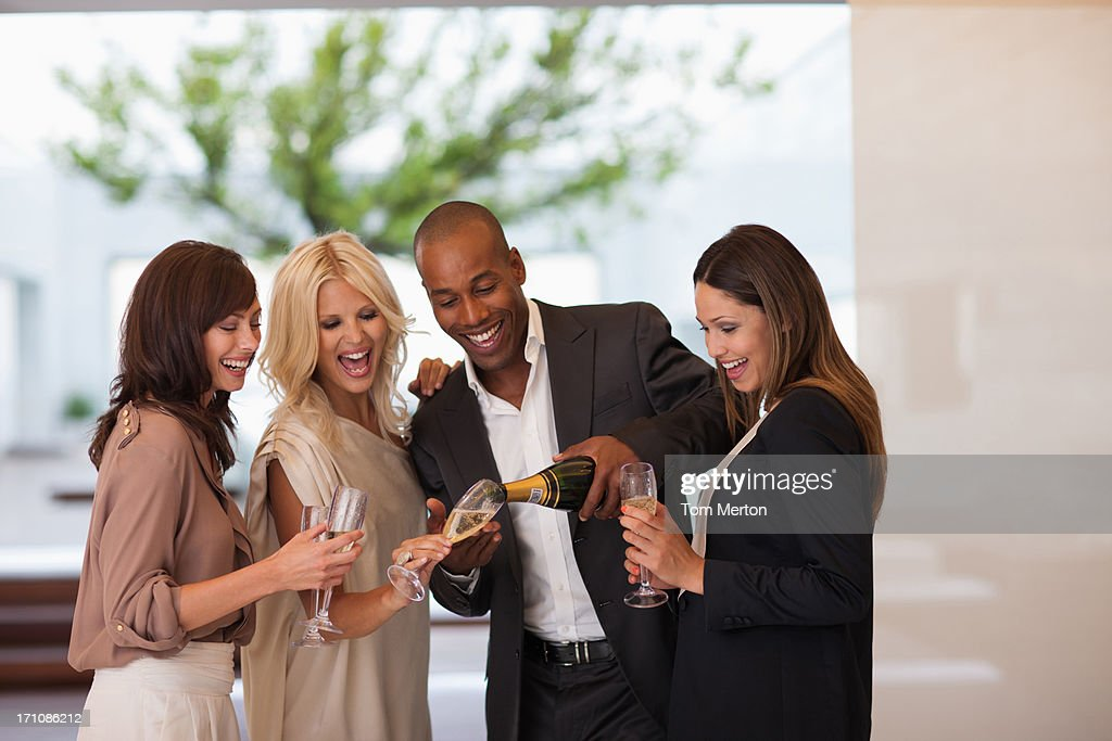 Friends pouring champagne : Stock Photo