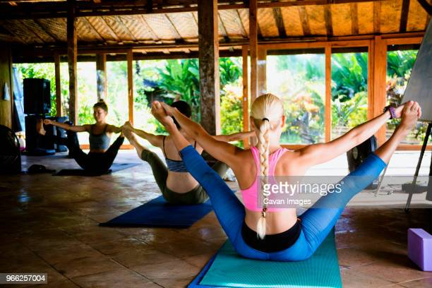 friends practicing pilates open leg rocker pose in yoga studio - legs spread open stock photos and pictures
