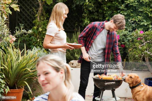Friends prepare food on barbecue while dog looks on at garden party.