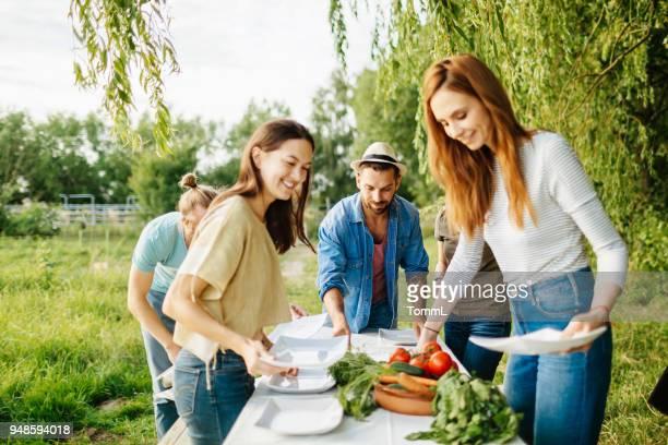 Freunde bereiten Mittagessen im Freien zu lokalen Farm
