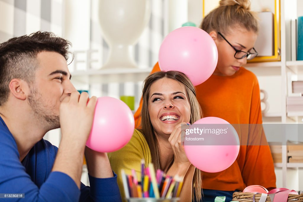 Friends preparing balloons  for party : Stock Photo
