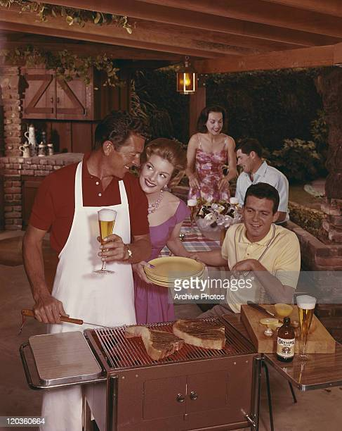 Friends preparing dinner on barbecue grill