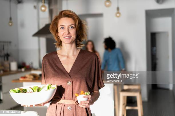 friends preparing dinner party in the kitchen, woman serving salad - 後ろボケ ストックフォトと画像