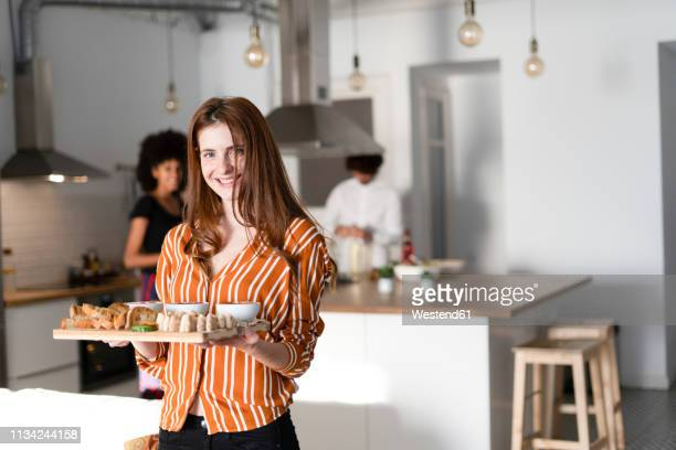 friends preparing dinner party in the kitchen, woman serving starters - serving food and drinks stock pictures, royalty-free photos & images