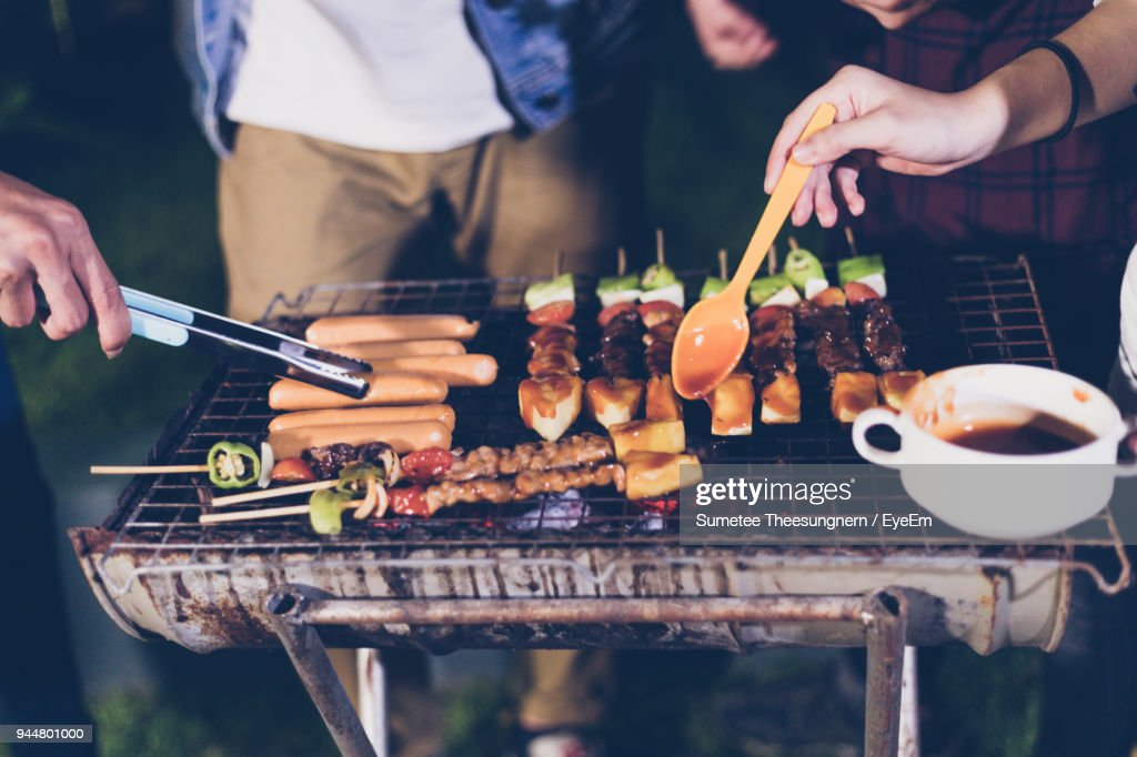 Friends Preparing Food On Barbecue Grill At Night : Stock Photo