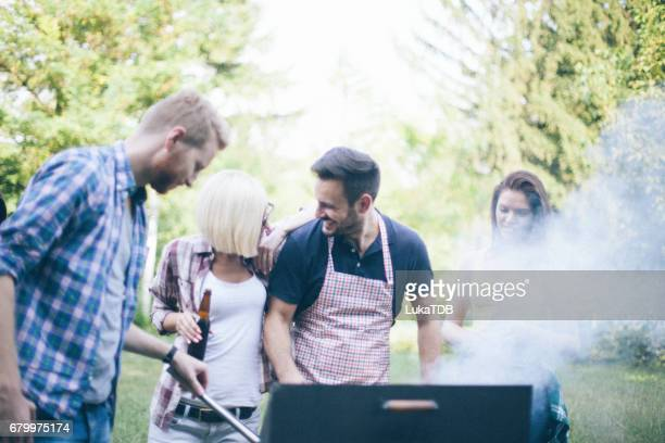 friends preparing food on grill - black shirt stock pictures, royalty-free photos & images