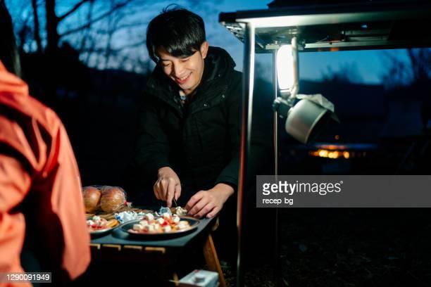 夜に自然の中でキャンプしながら食べ物を準備する友人 - evening meal ストックフォトと画像