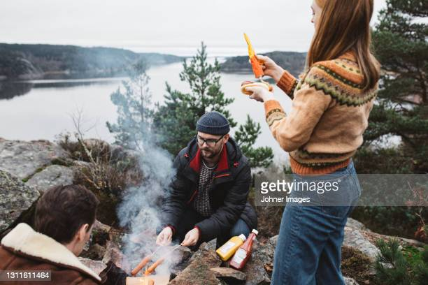 friends preparing hotdogs over campfire - sweden stock pictures, royalty-free photos & images